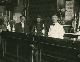 Bar scene interior with six men including the bartender. The poster on the mirrored back bar advertises James C. Dahlman for Governor.